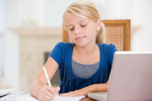 Young Girl Doing Homework And Using Laptop